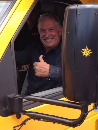 Most recent investor Gary Magness gives a thumbs-up while driving the Trans Tech Bus SST-e all-electric school ...