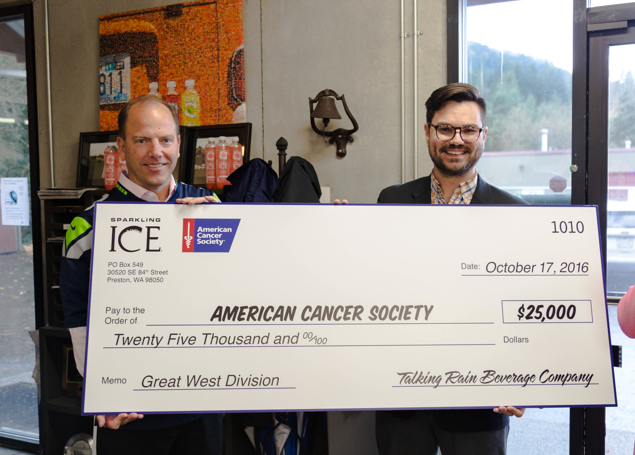 Kevin Klock, President and CEO of Talking Rain Beverage Co., presents check to Chase Carter of the American Cancer Society with the Great West Division.