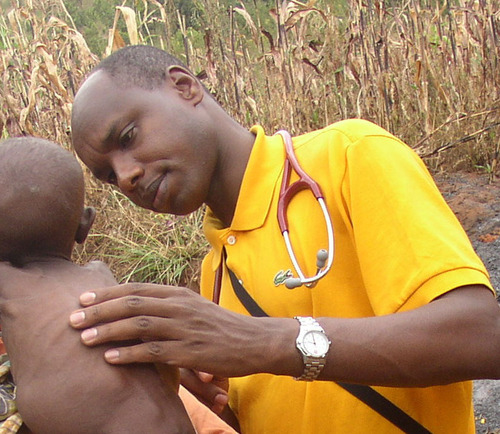 Deogratias Niyizonkiza, Founder and CEO, Village Health Works, attends to a malnourished child on a home visit ...