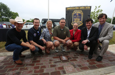 """Country music singer Justin Moore, NASCAR driver Kurt Busch, Armed Forces Foundation President and Executive Director Patricia Driscoll, Crown Royal Brand Director Abby Wise, Big Machine Label Group Founder and CEO Scott Borchetta and Indianapolis Motor Speedway COO Doug Boles pose with Retired Gunnery Sergeant Samuel Deeds (center), winner of Crown Royal's """"Your Hero's Name Here"""" program, behind the replica Yard of Bricks in Erlanger, Ky. on Thursday, June 27, 2013. As winner, Deeds will receive naming rights to the NASCAR Sprint Cup Series Race at Indianapolis Motor Speedway on July 28, 2013.  (PRNewsFoto/Diageo)"""