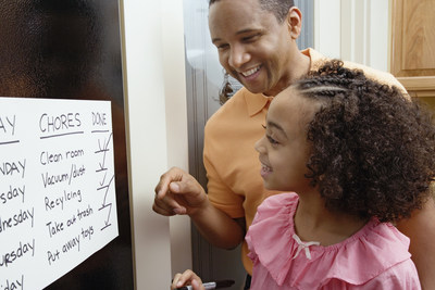 A dad and his daughter look at a chore chart