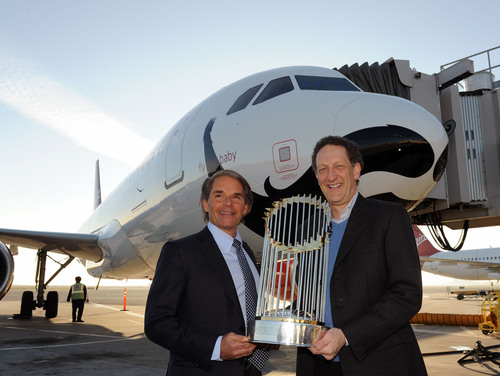 "In this photo released by Virgin America Airlines, Larry Baer, (right) president and CEO San Francisco Giants and David Cush (left) president and CEO of the airline, pose with baseball's World Championship Trophy, Thursday, January 17, 2013 at San Francisco International Airport. The World Championship Trophy traveled in a First Class seat onboard a new Virgin America Airbus aircraft ""Fly Bye Baby,"" named in honor of the SF Giants and painted with a beard across the aircraft nose -- a nod to the facial-hair friendly hometown ..."