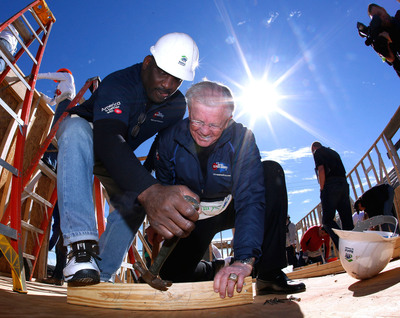 Former Washington MVP quarterback, Doug Williams, left, and former Washington coach, Joe Gibbs, celebrate the 25th anniversary of their historic Super Bowl win and help M&M'S launch their M' Prove America Campaign, which is designed to fund the construction of Habitat for Humanity homes across the country. Williams and Gibbs led a group of M&M'S associates and customers working on the future home of Ms. Gloria Smith. Join the 'M'Prove America(TM) movement at www.facebook.com/mms. (PRNewsFoto/Mars Chocolate North America) (PRNewsFoto/MARS CHOCOLATE NORTH AMERICA)