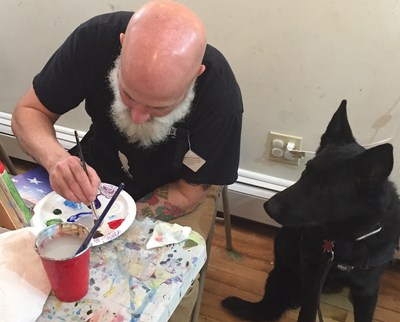 Service dog admires wounded veteran's painting techniques.