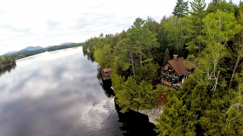 This rarely offered year-round Adirondack home on Ampersand Bay on the north end of Saranac Lake in an ...