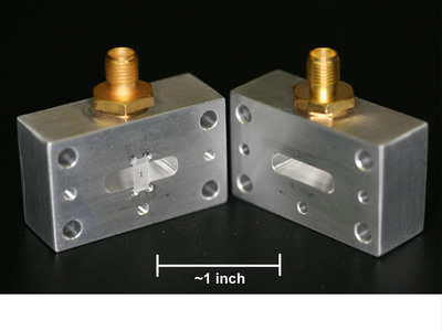 """A picture of IBM's """"3D"""" superconducting qubit device where a qubit (about 1mm in length) is suspended in the center of the cavity on a small Sapphire chip. The cavity is formed by closing the two halves, and measurements are done by passing microwave signals to the connectors. Despite the apparent large feature size (the cavity is about 1.5 inches wide) for this single qubit demonstration, the team believes it is possible to scale such a system to hundreds or thousands of qubits. (PRNewsFoto/IBM)"""