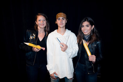 Pencils of Promise executives Leslie Engle Young (L) and Natalie Ebel (R) present Justin Bieber with the first-ever Pencils of Promise Global Ambassador award just prior to his sold out show at the Barclays Center in Brooklyn, New York on May 4. (Credit: Rory Kramer)