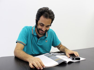 Blind person reading a magazine using Horus.