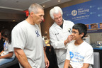 New York Yankees manager Joe Girardi, left, and Bill Austin, Founder of Starkey Hearing Foundation, celebrate as Afzal Ali, 12, of Queens, NY receives the gift of hearing at the Foundation's New York Hearing Mission on June 28th at Yankee Stadium. (PRNewsFoto/Starkey Hearing Foundation, Diane Bondareff)