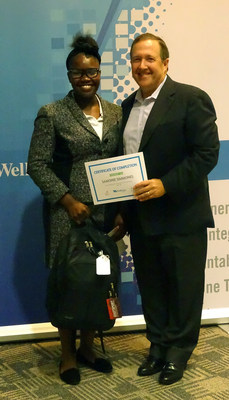 On Aug. 1, 16-year-old Samonie Simmons accepts her graduation certificate from WellCare CEO Ken Burdick.