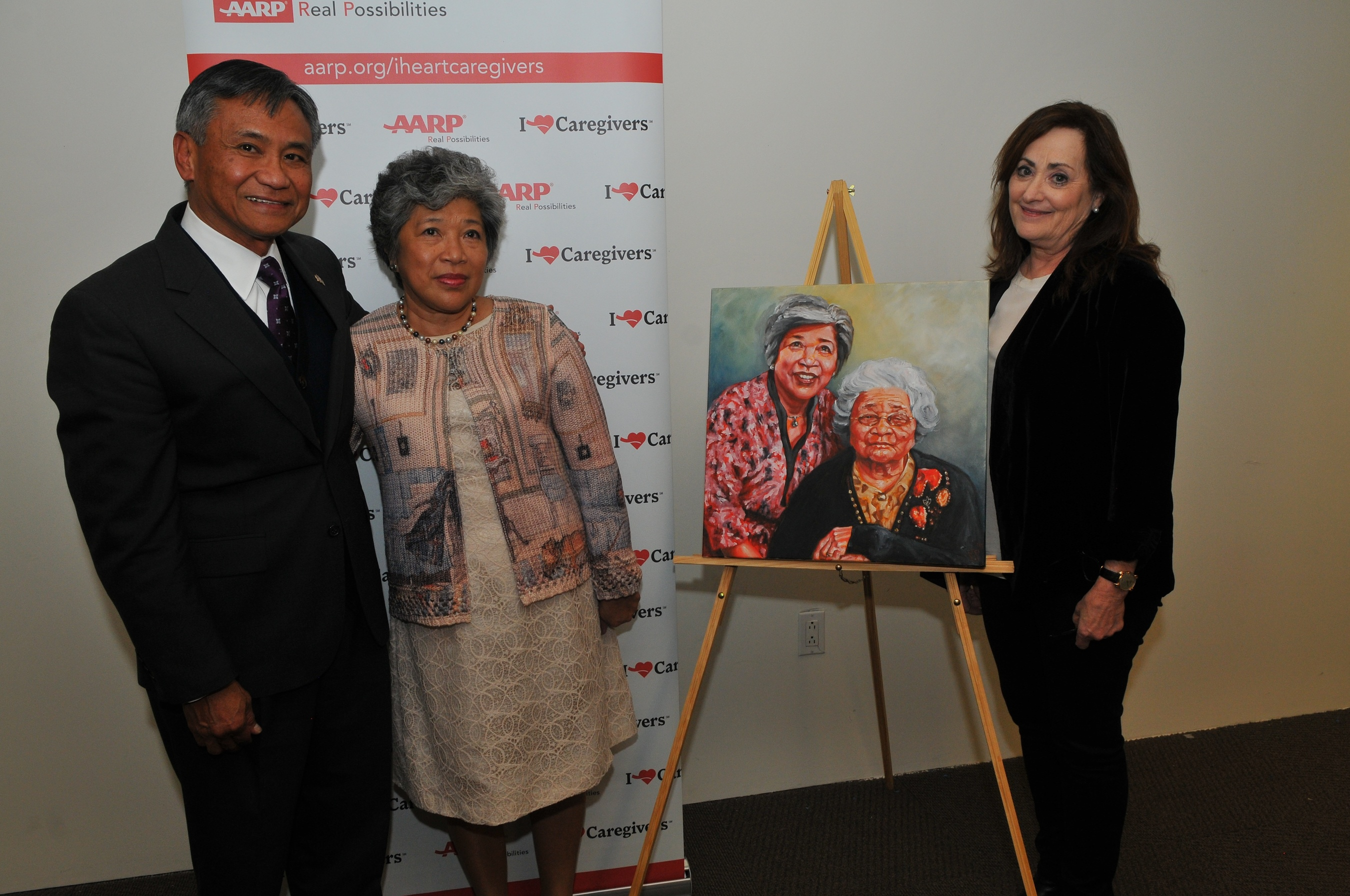 """AARP New York State Director Beth Finkel (R) with """"Portrait of Care"""" she presented to family caregiver Editha Batalla Santiago (L) of Hollis, Queens, standing with AARP Community Ambassador and family caregiver advocate Retired Major Gen. Antonio Taguba."""