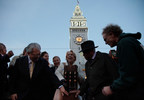 """San Francisco Chief of Protocol Charlotte Shultz (center) joins Mayor Ed Lee (left) and former Mayor Willie Brown (right) in """"flipping the switch"""" to turn on the lights to the Ferry Building as it is re-lit to appear as fairgoers would have seen it in 1915. Looking on is steeplejack Jim Phelan (far right) who built the numbers and installed the light bulbs, which will adorn the Ferry Building until December 4.Photo Credit: Michael Tweed."""