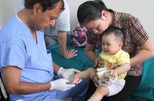 AOFAS volunteer Naren Gurbani, MD, evaluates a baby's clubfoot in Thai Nguyen, Vietnam. (PRNewsFoto/AOFAS)