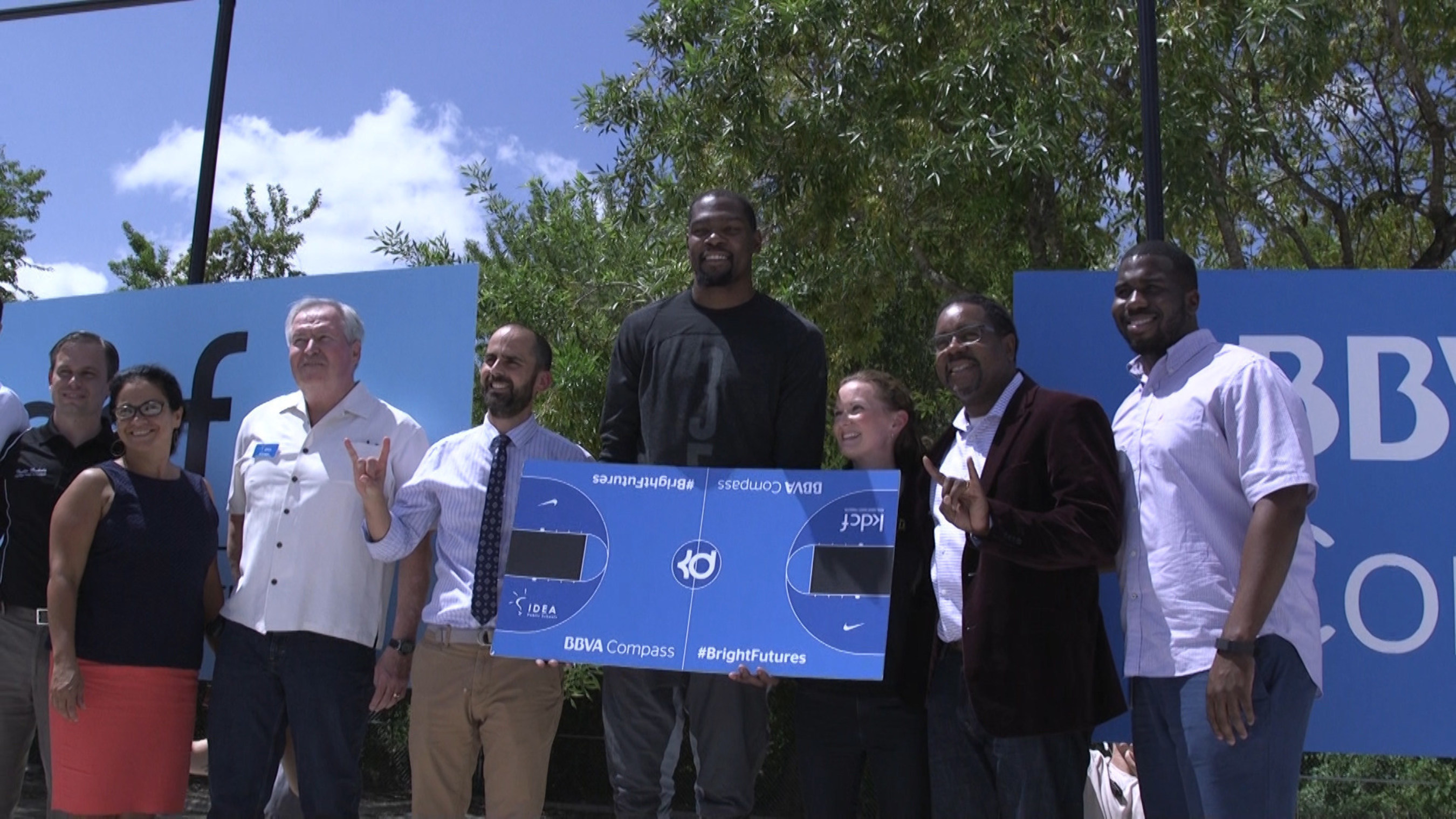 NBA All-Star Kevin Durant poses with IDEA Public Schools Austin Executive Director (left of Durant) and the IDEA Public Schools Austin Regional Board at the construction site of IDEA Rundberg Public School's new outdoor basketball court.