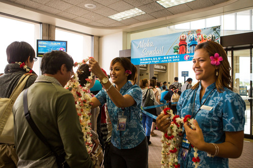 Hawaiian Airlines Customer Service Agents Starlynn Kuaana (left) and Charael Perry (right) greet passengers ...