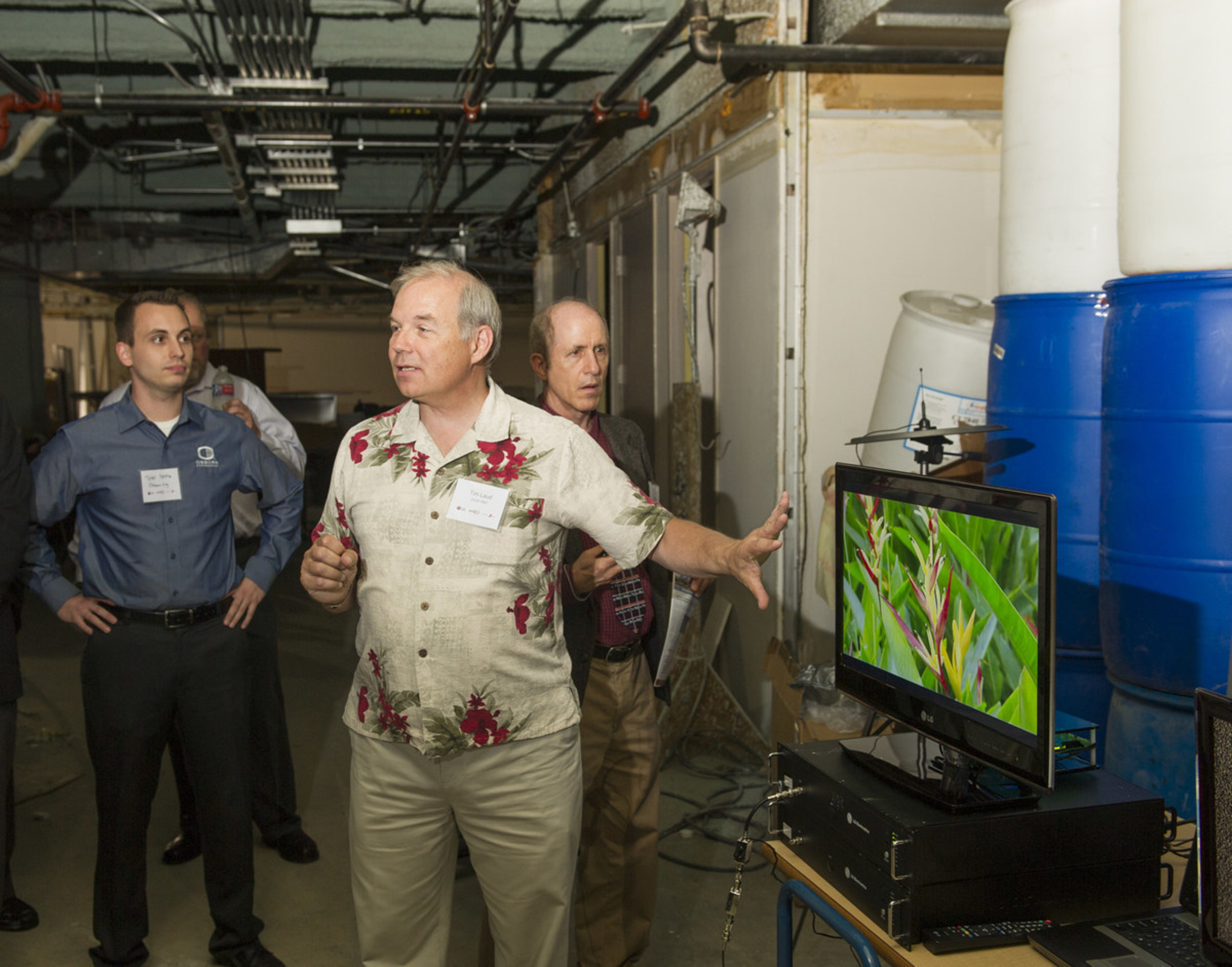 """Zenith engineer Tim Laud explains how the future """"ATSC 3.0"""" next-generation television broadcast standard will deliver signals for superior deep indoor reception as seen in the basement of a commercial building in downtown Cleveland where LG Electronics and GatesAir have been field-testing their new technology. (Photo by Phil Long/AP Images for LG Electronics USA)"""