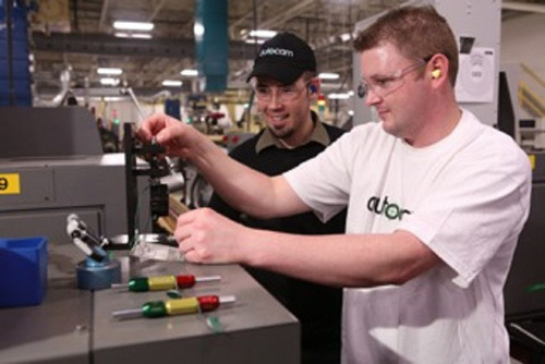 """Learn and Earn"" in action: Autocam AMP students running state of the art machining centers.(PRNewsFoto/Autocam Corp.)"