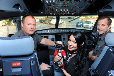 """Virgin America Captain Scott Corley  (left) and First Officer Dennis Calnan (right) welcome one of ten Chihuahua pups being flown to EWR onboard Virgin America's fifth """"Operation Chihuahua"""" airlift.  (PRNewsFoto/Virgin America)"""