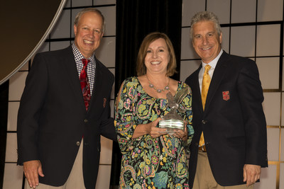 Becky Gennings of Varsity Brands accepts the American Tradition Award from Bob Gardner and Tom Mezzanote of the National Federation of State High School Associations during the Association's 96th annual Summer Meeting in New Orleans.