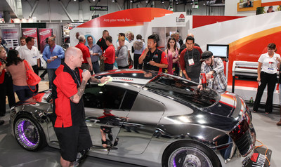 Las Vegas—The one-of-a-kind West Coast Customs, Tron Audi R8 shines at the 2014 SEMA (Specialty Equipment Marketing Association) Show as Neil Tinsley, of Findlay Customs in Henderson, NV applies LLumar® CTX® window tint to the back window to help protect the interior and passengers from UV rays. Award-winning window tinter, Randy Humphries, looks on as he shares his personal installation tips with the audience.