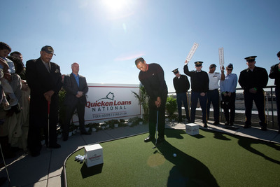 Tiger Woods putts to pay a veteran's monthly mortgage payment at the announcement of the Quicken Loans National golf tournament