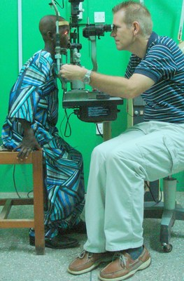 Donald L. Budenz, M.D., recipient of the 2014 Outstanding Humanitarian Award, examines a patient's eyes in Ghana (PRNewsFoto/AAO)