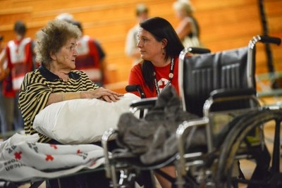 Clendenin, West Virginia resident Lucille Chandler is safe and dry in a Red Cross shelter in Charleston. Here she tells Red Crosser Joanna King how her home flooded and she and her daughter were rescued by boat. The Red Cross provided her with a wheelchair to help her get around. Red Cross Photo by Daniel Cima.