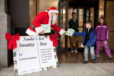 """A costumed Santa outside the New York headquarters of luxury developer TF Cornerstone hands young passersby fliers explaining why the developer has landed on Santa's """"naughty.""""  The Santa and his helpers are with Local 32BJ of the Service Employees International Union, which says Cornerstone is undermining area standards for New York's working people.  (PRNewsFoto/SEIU Local 32BJ)"""