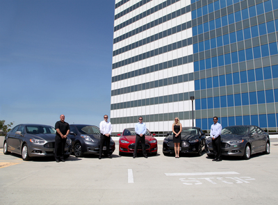 Consistent with the company's environmental mission, WASH executives have made a personal commitment to reduce carbon emissions by driving electric vehicles. Pictured here (left to right) Ross Van Horne, John Buccola, Adam Coffey, Cathy Jackson and Tomy Joseph pose with their electric vehicles. (PRNewsFoto/WASH Multifamily Laundry Systems)