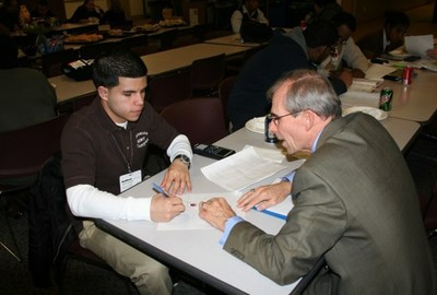 Aponte works on homework in 2010 with Stand & Deliver mentor Steve Horlitz. (PRNewsFoto/Raytheon)