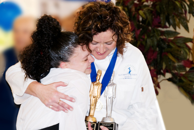 Chef Lisa Archer, newly-crowned Ultimate Chef America, hugs server Ashley Maufroy of Grand Court Tavares.(PRNewsFoto/Brookdale Senior Living)