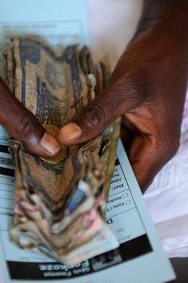 A man holds Haitian money. Photo credit: Darcy Kiefel.  (PRNewsFoto/CGAP)