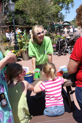 Families transform empty GoGo squeeZ(TM) pouches into planters at the Backyard Play Garden presented by GoGo squeeZ(TM) at the Epcot(R) International Flower & Garden Festival, highlighting their ongoing commitment to the planet and helping families lead healthier lifestyles.  (PRNewsFoto/GoGo squeeZ)