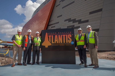 Kennedy Space Center Visitor Complex officials unveil the logo and announce the $100 million home of Space Shuttle Atlantis, seen in the background, will open June 29. From left to right: Space Shuttle Astronaut Jon McBride, Visitor Complex Chief Operating Officer Bill Moore, Delaware North Companies Parks & Resorts President Rick Abramson, Visitor Complex Director of Project Development and Construction Tim Macy and PGAV Destinations Principal Mike Konzen. Delaware North operates the visitor complex for NASA, and PGAV Desitnations designed the exhibit.   (PRNewsFoto/Kennedy Space Center Visitor Complex)