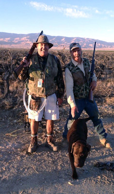 Bob Coyle, left, without a human heart goes hunting with his friend since age ten, Jeff Galieti. Bob's dog Diesel joins in the hunt. Coyle is seen with the air tubes that connect the SynCardia Heart to the Freedom(R) portable driver that he carries in a backpack.