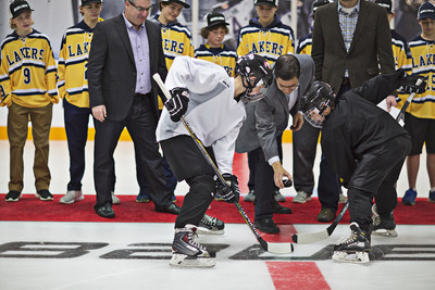 Amir Rosenthal, President of PSG Brands, drops the ceremonial puck to inaugurate the in-store BAUER rink in Bloomington, Minn., along with several 2015 Minnesota state championship youth players who participated in the ceremony that featured James Bohn singing the national anthem.