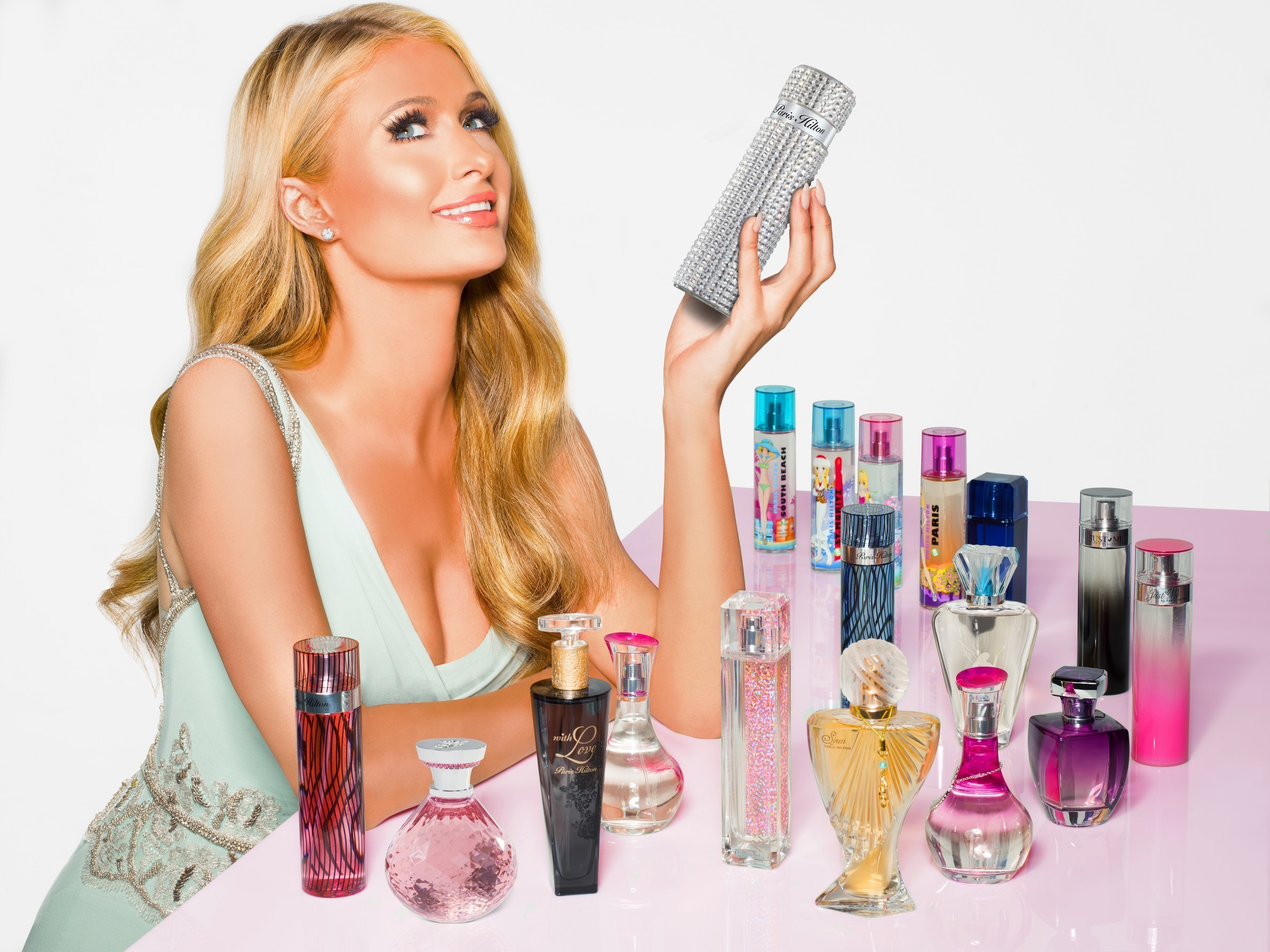 Paris Hilton with her 18 fragrances from her collection.