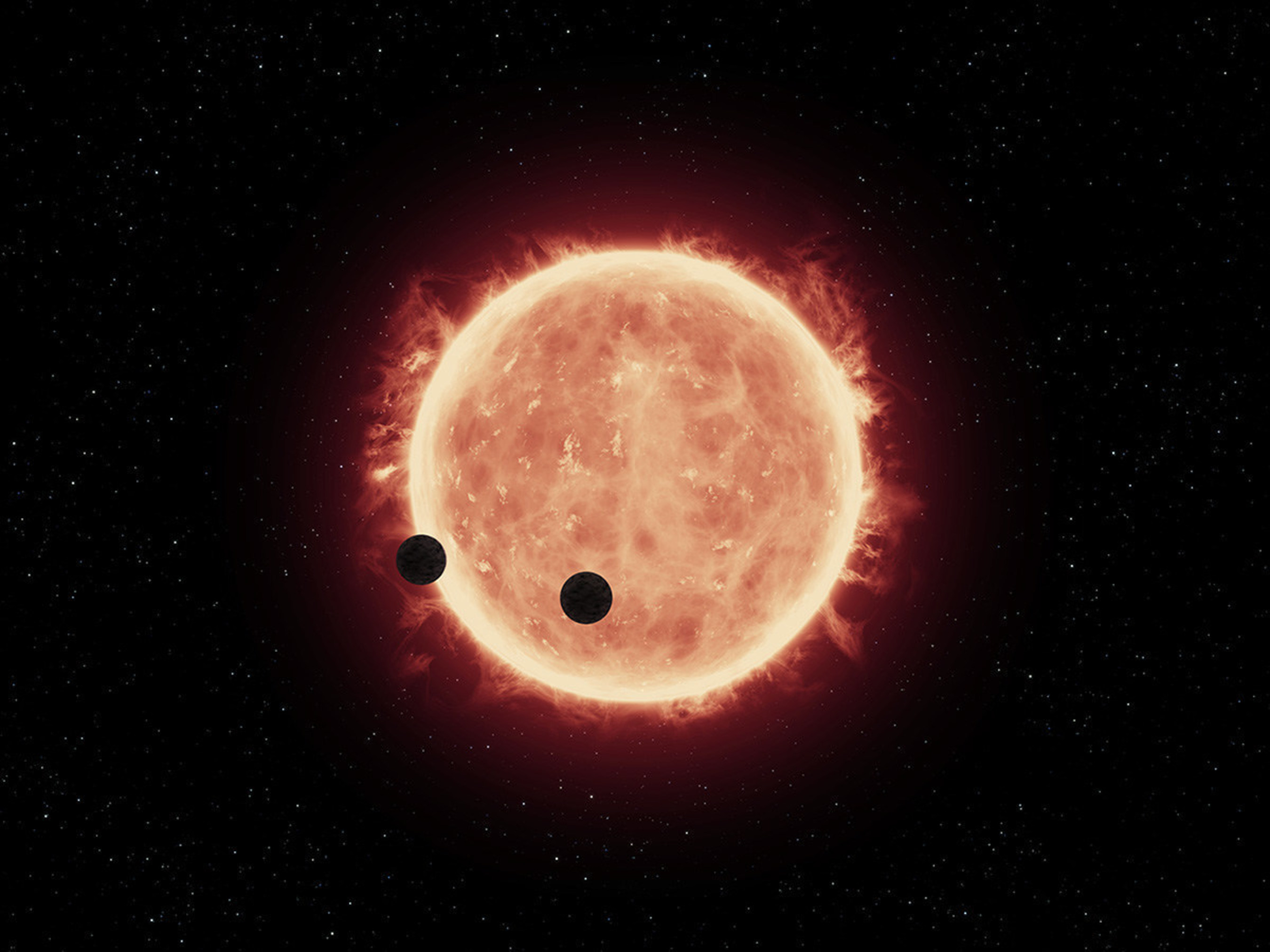 This artist's illustration shows two Earth-sized planets, TRAPPIST-1b and TRAPPIST-1c, passing in front of their parent red dwarf star, which is much smaller and cooler than our sun. NASA's Hubble Space Telescope looked for signs of atmospheres around these planets.
