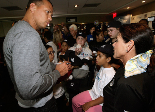 Yankees third baseman Alex Rodriguez and co-founder of Starkey Hearing Foundation Tani Austin help patients hear for the first time at the Foundation's New York Hearing Mission at Yankee Stadium.  (PRNewsFoto/Starkey Hearing Foundation)