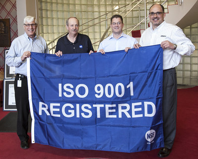 (From left) Zippo Quality Control Engineer Dana Barre, NSF International's lead ISO 9001:2008 auditor Garry Puglio, Zippo VP of Operations Tim Van Horn, and Zippo President Mark Paup unfurl the ISO 9001:2008 flag at Zippo's headquarters in Bradford, PA, signifying that Zippo's quality management system meets international standards which ensure excellence, consistency and efficiency.