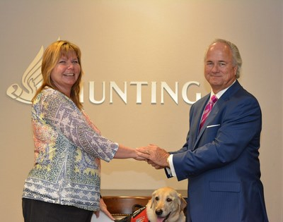 Dennis Proctor, (right) Chief Executive of Hunting PLC, presents Lori Stevens, (left) Founder and Executive Director of Patriot PAWS Service Dogs, with a donation of $150,000.  The gift was given on behalf of the 2015 Hunting Art Prize to support the nonprofit's efforts in providing service dogs at no cost to disabled American veterans and others with mobile disabilities.