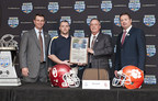 The 2014 Russell Athletic 'Fight Like Dylan Award' is presented to Shoreham-Wading River High School, Shoreham, N.Y. during the 2014 Russell Athletic Bowl Press Conference; L-R, Clemson University head coach Dabo Swinney; Russell Athletic senior vice president, general manager, Robby Davis; Shoreham-Wading High School assistant coach Tom Fabian; University of Oklahoma head coach Bob Stoops.