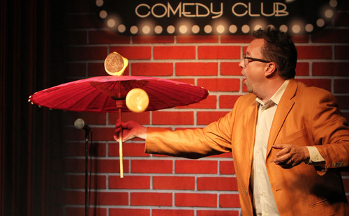 Michael Rayner (Host of our Family Friendly Show Two Milk Minimum) Spins a Cheeseburger on an Umbrella.  (PRNewsFoto/Flappers Comedy Club)