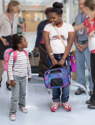 Lexi Henderson, with sister Sapphire Colston by her side, bids farewell to University of Florida (UF) Health Shands Children's Hospital as the youngest SynCardia Total Artificial Heart patient to be discharged from a hospital using the Freedom portable driver. The SynCardia Heart powered by the Freedom portable driver allows her to live a near-normal life as she waits for a matching donor heart. (PRNewsFoto/SynCardia Systems, Inc.)