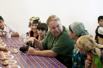 "Photographer and philanthropist Howard G. Buffett meets with children receiving food aid at a school in Tajikistan. On Sept. 18, 2015, the Newseum will open ""40 Chances,"" an exhibit of Buffett's photos chronicling the world hunger crisis. Credit: Howard W. Buffett"