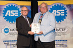 Dan Rowland accepts the Gates Tools for Schools/ASE Instructor of the Year award from Bobby Bassett of Gates Corporation.