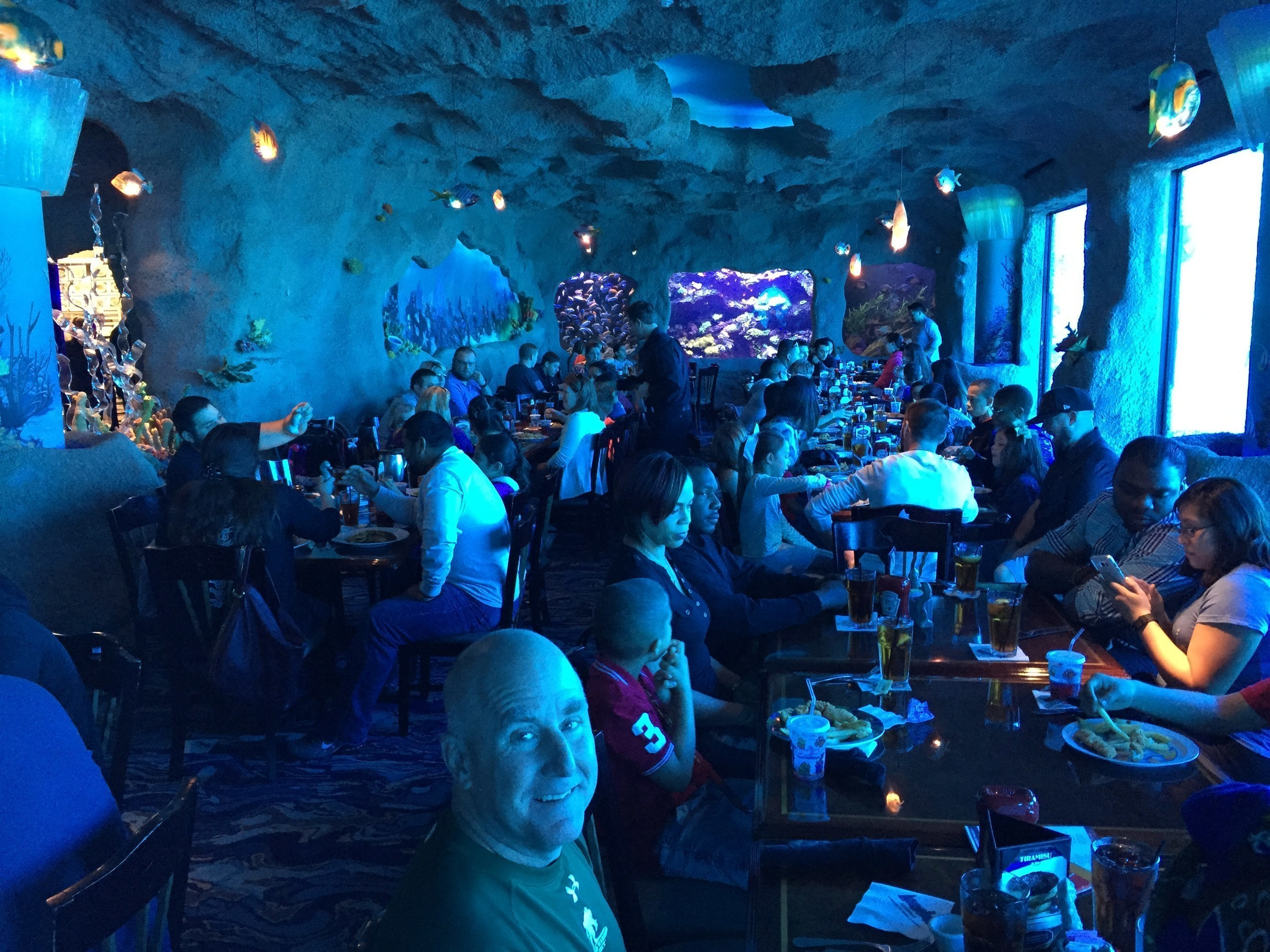 Wounded Warrior Project Alumni and their families enjoy a meal among the fishes at the Kemah Aquarium, during an Alumni Program event.