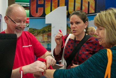 Jeff Bartle of 3D Exhibit helps visitors put on their RFID/NFC wristbands at EXHIBITOR 2015 trade show
