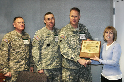 "U.S. ARMY SAYS ""THANKS"" - LTC David Roscoe presents UniFirst General Manager Suzanne Northern with a handcrafted plaque in appreciation for morale-boosting T-shirts the company donated to the 718th Transportation Battalion. Looking on are CPT Jeff Hastings (left) and CSM Bruce Clark. (UniFirst Photo).  (PRNewsFoto/UniFirst)"