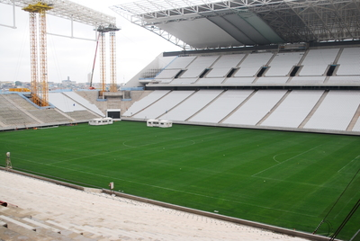 The grass surface of the stadium of Corinthians, Sao Paulo,  2014  FIFA World Cup stadium is currently  being installed.Desso GrassMaster is a hybrid grass system: a 100 % natural grass field reinforced by 20 million artificial  fibres. The machines ( protected by tents) inject the artificial fibres every 2x2cm about 18 cm deep into the soil. dessosports.com